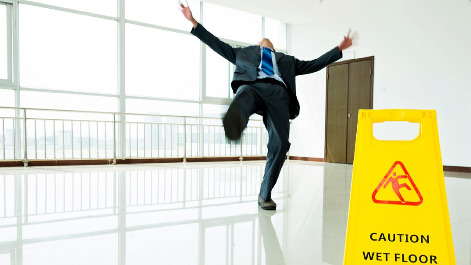 Businessman Slipping On A Wet Floor Stock Photo