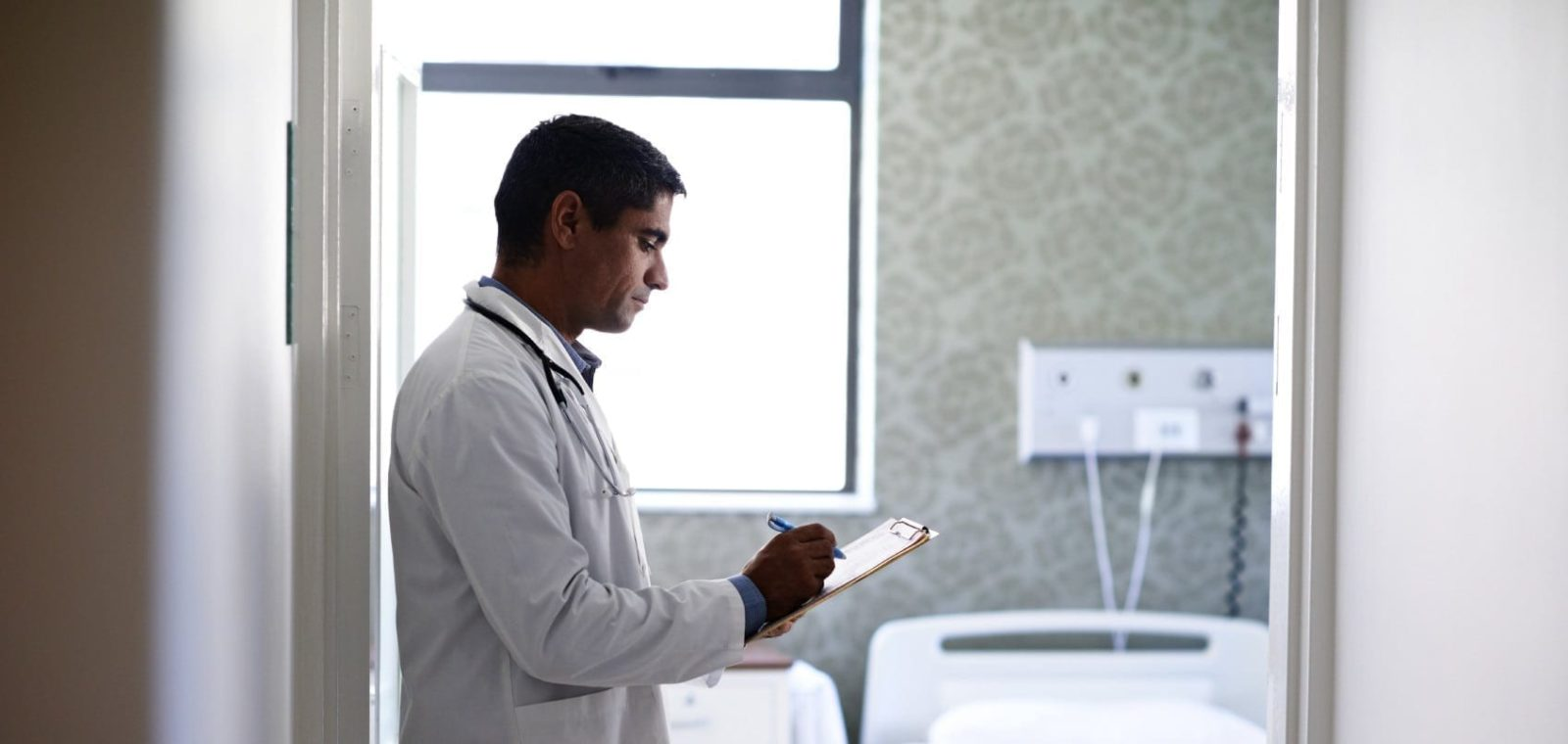 Doctor Completing Medical Forms Stock Photo