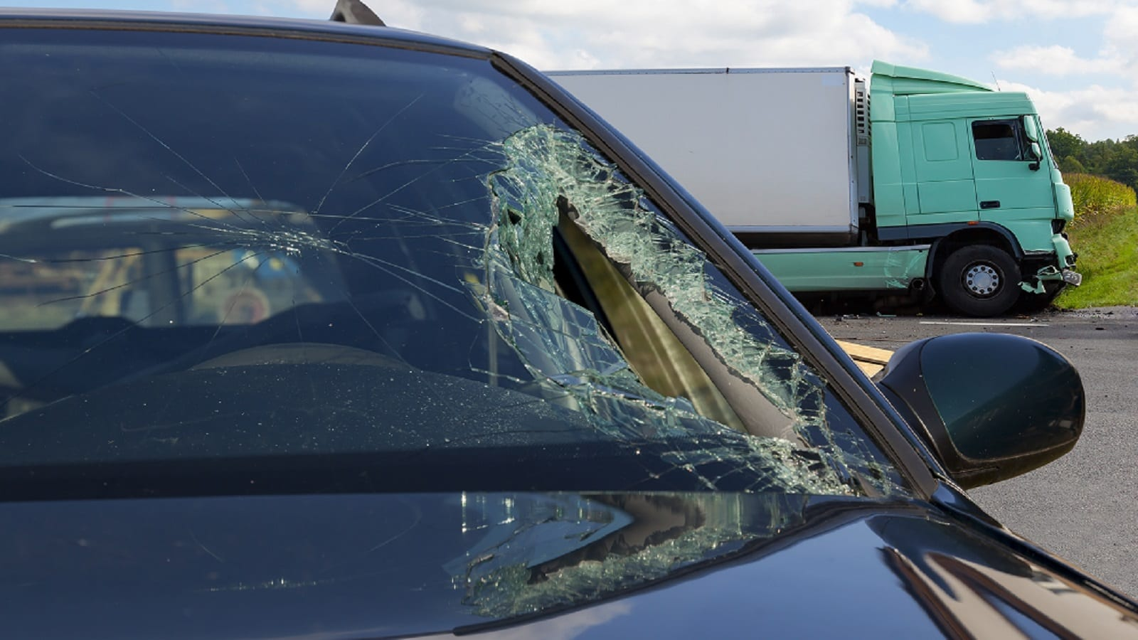 View of truck in an accident with car, broken glass