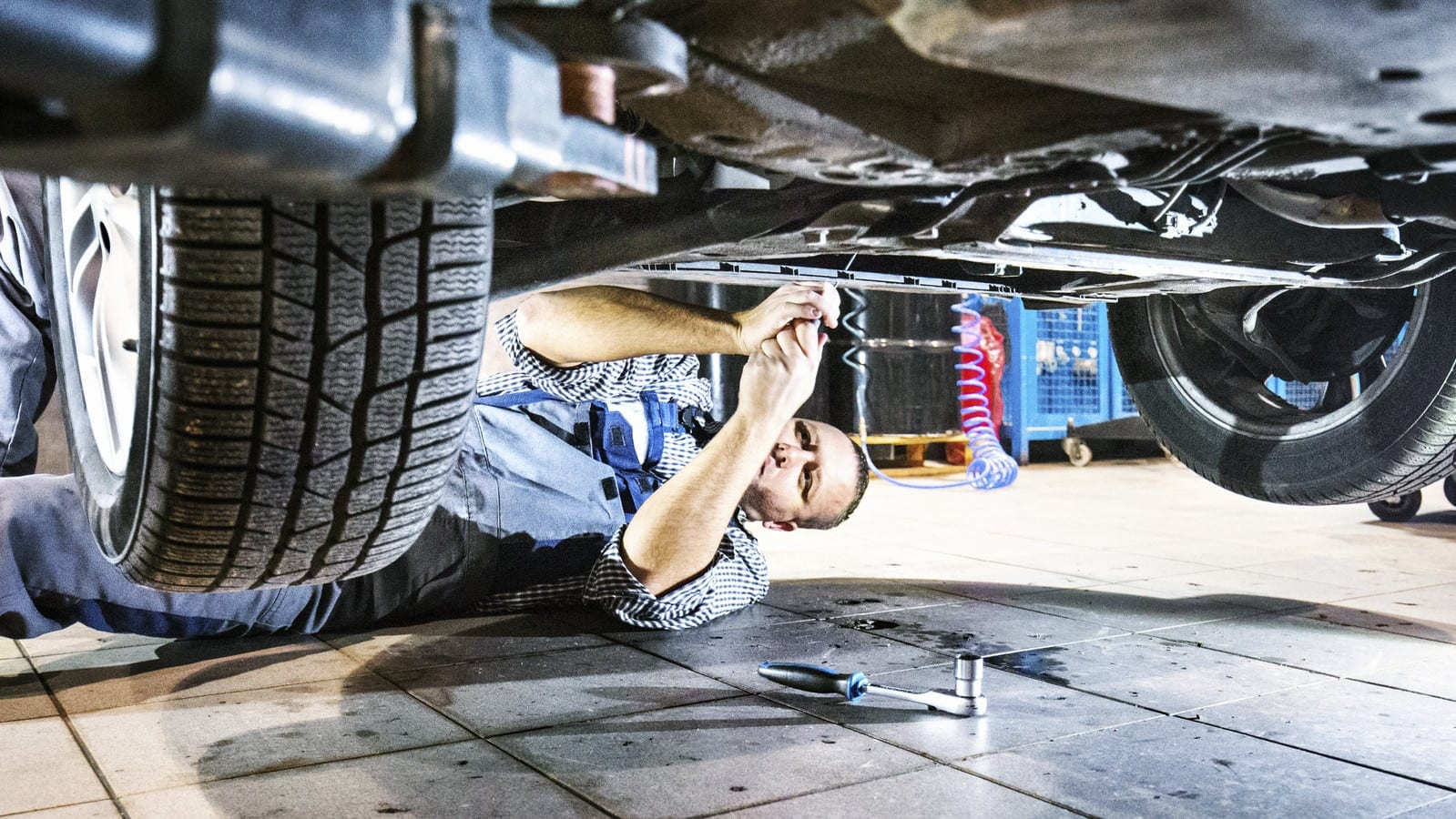 Mechanic Working Underneath A Vehicle In An Auto Body Shop Stock Photo