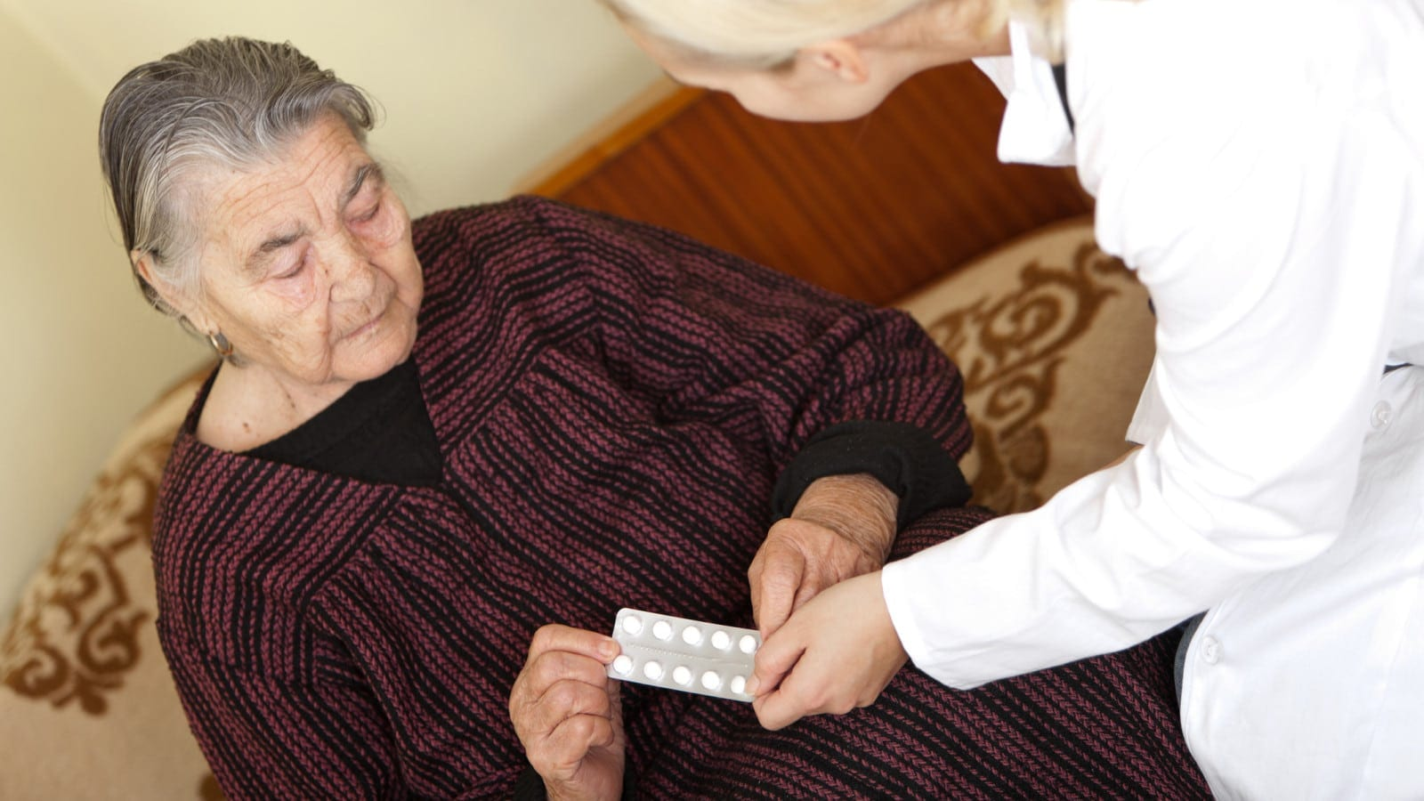 Doctor Giving Medication To Elderly Woman Stock Photo