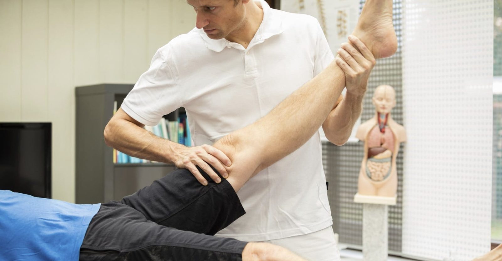 Physician Examining A Patient's Leg Stock Photo