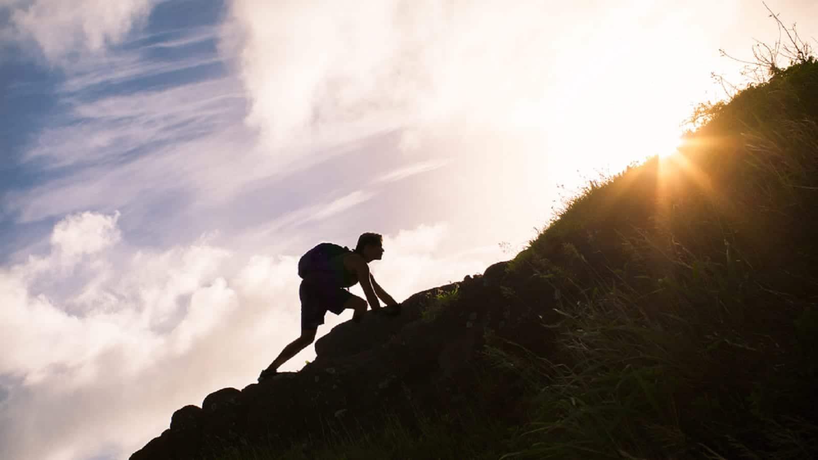 Young Man Climbing A Steep Mountain Stock Photo