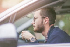 man in glasses driving car looking bored