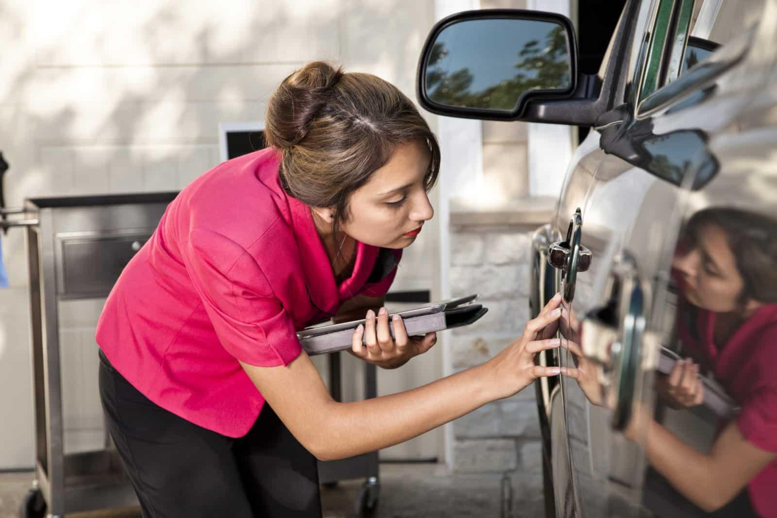 insurance adjuster inspecting car accident damage