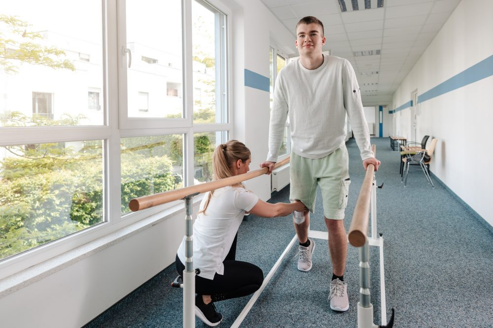 A young man going through physical therapy after suffering a personal injury.